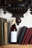 pic of pendulum clock  - Bottle of craft beer with blank label template standing on a shelf with books under an old clock - JPG