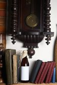 image of pendulum clock  - Bottle of craft beer with blank label template standing on a shelf with books under an old clock - JPG