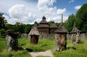stock photo of farmworker  - Medieval wooden church with old apiary Ukraine, Pirogovo park, unesco heritage site,  Europe
