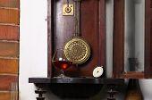 picture of pendulum clock  - Glass of brandy standing inside an old clock - JPG