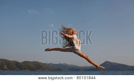 The jump flight above the sea and mountains of the young girl