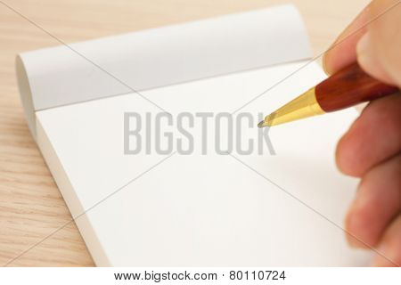 Blank memo pad and a hand holding a pen.
