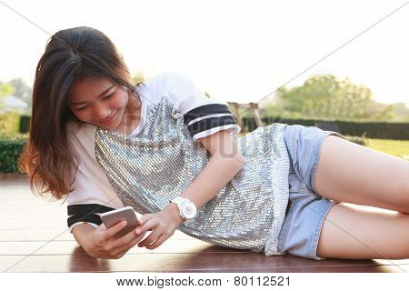 Portrait Of Young Beautiful Woman Lying And Reading Text On Smart Phone Screen And Smiling With Happ
