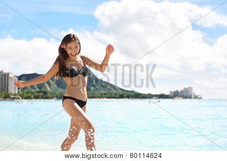 Beach woman in bikini on Waikiki, Oahu, Hawaii, USA. Girl on travel vacation holidays running having fun splashing water on Hawaiian Waikiki beach with Diamond Head mountain. Asian Caucasian model.