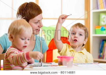 cute mother teaching her kids to paint