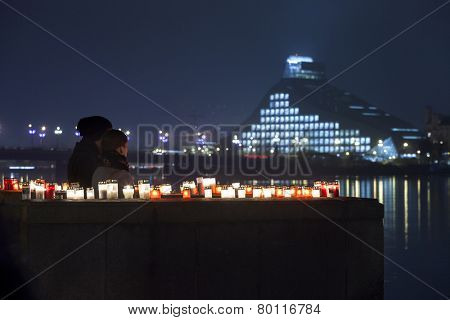 RIGA, LATVIA - NOVEMBER 11: Unidentified couple at commemoration of Soldiers Memorial Day. People light candles to honor victory over Russian German militia - keypoint in birth of Republic of Latvia