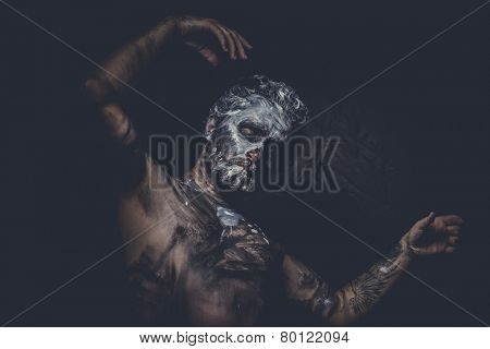 naked man covered with paint and mud skin