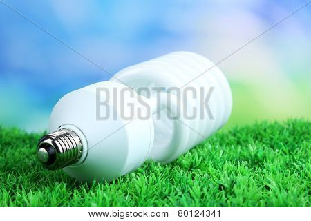 Energy saving light bulb on green grass, on bright background