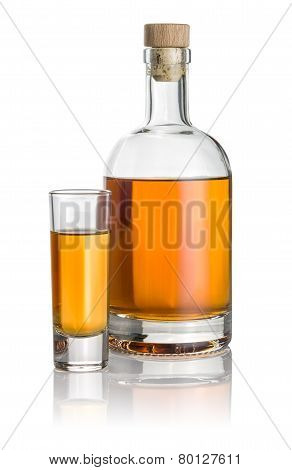 Bottle and high shot glass filled with amber liquid
