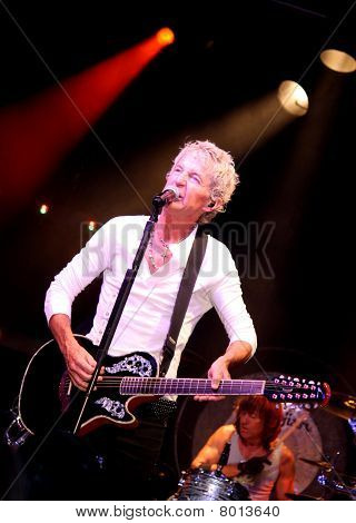 Kevin Cronin cantando & tocando guitarra