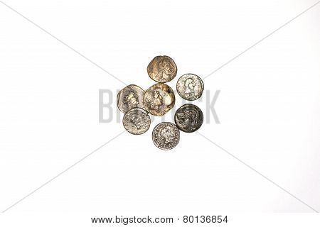 Seven Ancient Coins On A White Background