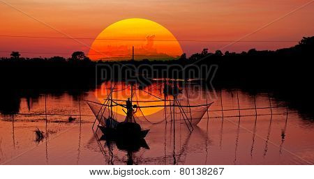 A fisher man in the river with sunset sky