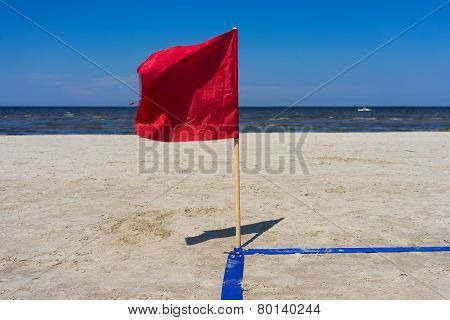 Red Flag In The Wind On The Sandy Beach