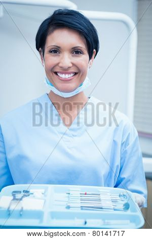 Portrait of female dentist in blue scrubs holding tray of tools