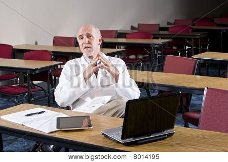 Mature Male Scientist Sitting In Conference Room