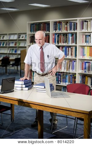 Mature Man Researching Books In Library