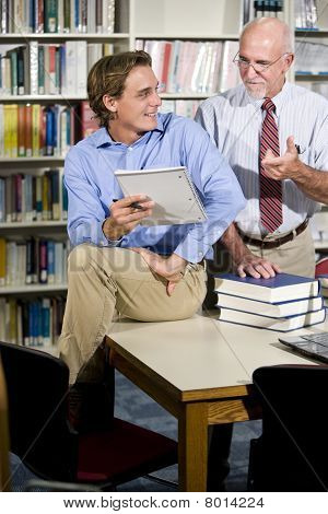 College Teacher And Student Talking In Library