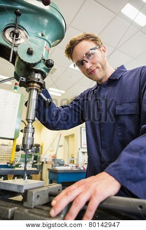 Engineering student using large drill at the university
