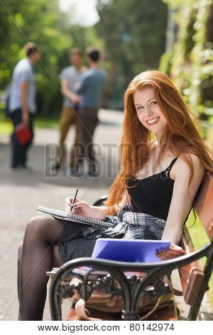 Pretty student studying outside on campus at the university