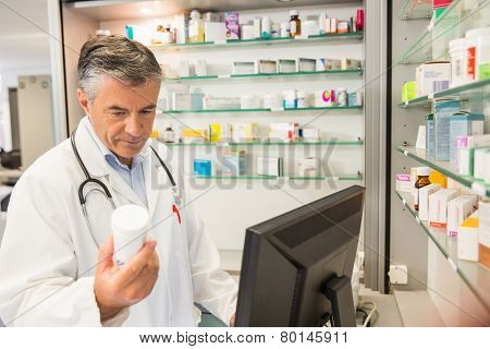 Senior pharmacist using the computer at the hospital pharmacy