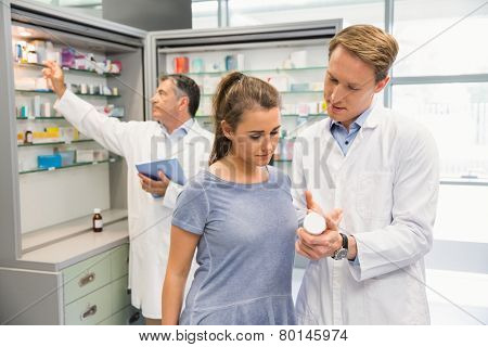 Happy customer talking with pharmacist at the hospital pharmacy
