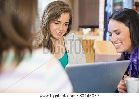 Young students doing assignment on laptop together at the university