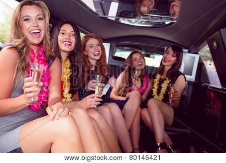 Happy friends drinking champagne in limousine on a night out