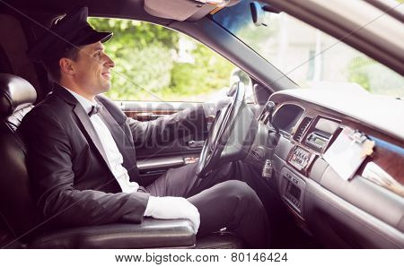 Limousine driver driving and smiling in his limousine
