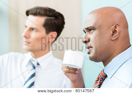 Two business people, Indian and Caucasian, having informal coffee meeting