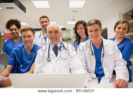 Medical students and professor using laptop at the university