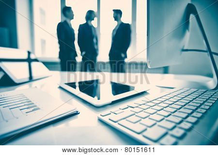 Touchpad, monitor, keypad and business document with group of businessmen on background
