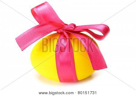 Close-up of yellow Easter egg tied up by pink ribbon