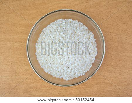 White dry uncooked rice in bowl on wooden background.