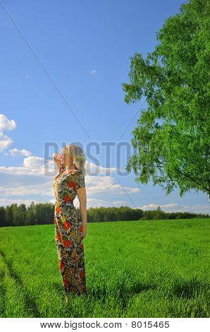 Woman On The Grass Field And A Sunset