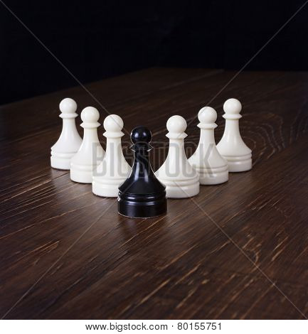Black Pawn In Focus On A Background White Pawns.