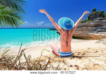 Woman in hat enjoying sun holidays on the beach of Mexico