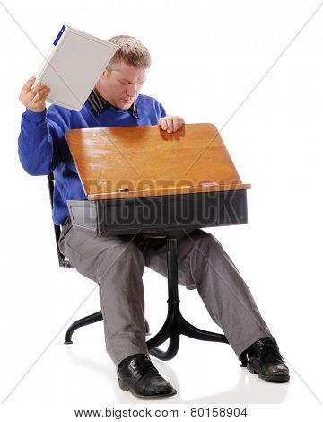A mature adult student pulling supplies out of the retro child's school desk in which he's sitting.  On a white background.