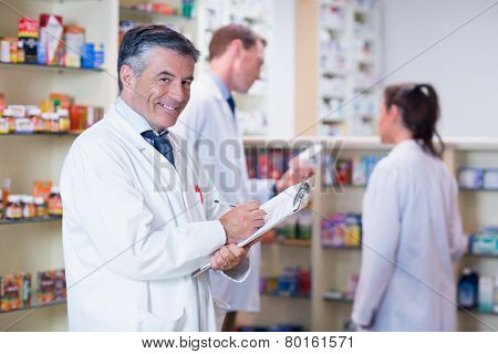 Smiling pharmacist in lab coat writing a prescription in the pharmacy