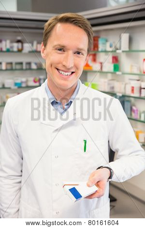 Happy pharmacist holding medicine boxes at the hospital pharmacy