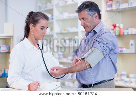 Trainee listening to patients pulse with stethoscope in the pharmacy