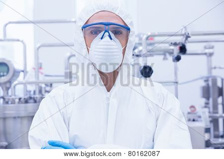 Portrait of a scientist standing with arms crossed in the factory