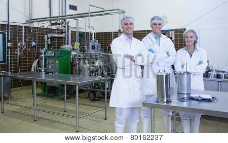 Biologist team with arms crossed smiling at camera in the factory
