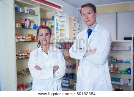 Pharmacist and his trainee standing with arms crossed in the pharmacy