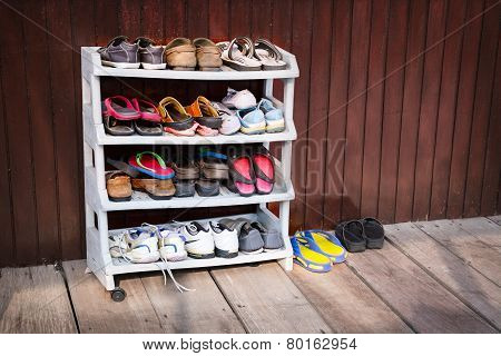 Colorful Shoes On A Plastic Shoe Rack Outside A House