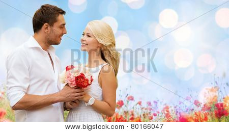 holidays, summer, people and dating concept - happy couple with bunch of flowers over lights and poppy field background