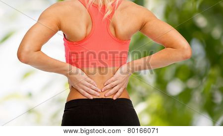 fitness, healthcare and medicine concept - close up of sporty woman touching her back