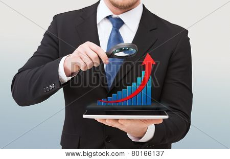 technology, development, analytics , people and business concept - close up of businessman holding magnifying glass over tablet pc computer and growth chart