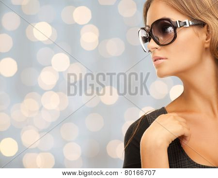 people, fashion, elegance and style concept - close up of beautiful young woman in shades over holidays lights background