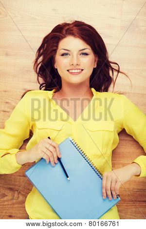 education and home concept - smiling redhead female student lying on floor with textbook and pencil