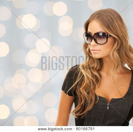 people, fashion, elegance and style concept - beautiful young woman in shades over holidays lights background